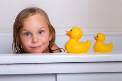 Baby girl taking bath with foam and toys. Cute happy baby girl taking bath with foam and toys, child`s hygiene, healthy lifestyle, carefree childhood concept stock photos
