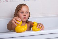 Baby girl taking bath with foam and toys. Cute happy baby girl taking bath with foam and toys, child`s hygiene, healthy lifestyle, carefree childhood concept stock photo