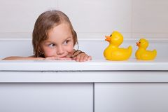 Baby girl taking bath with foam and toys. Cute happy baby girl taking bath with foam and toys, child`s hygiene, healthy lifestyle, carefree childhood concept Royalty Free Stock Photos
