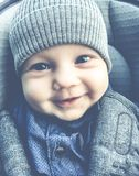 Cute happy baby smiling outdoors closeup. Cute baby in a baby car seat closeup stock image