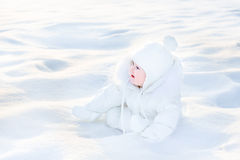 Cute happy baby in snow on sunny winter day Royalty Free Stock Photo