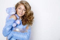 Cute, happy blonde young girl holding teddy bear . Beauty and joyful girl stock photo