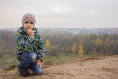 Cute happy boy child outdoors. Misty wood on the background. Stylish baby boy having fun outside in the park. Cute happy boy child outdoors. Misty wood on the Royalty Free Stock Photography