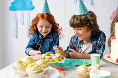 cute happy boy and girl in party cones eating sweets at birthday Stock Photography