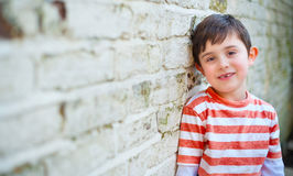 Cute happy boy leaning against brick wall. This is a picture of a cute six year old boy leaning against a white grungy brick wall. He has a new tooth growing stock photography