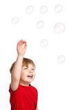 Cute Boy playing Bubbles. Cute Happy boy playing with bubbles shot in the studio on a white background Royalty Free Stock Photo