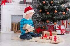 Cute boy in santa hat unwrapping christmas presents Stock Photography
