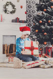 Cute happy boy in santa hat unwrapping christmas presents Royalty Free Stock Image