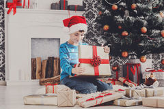 Cute happy boy in santa hat unwrapping christmas presents Stock Photos