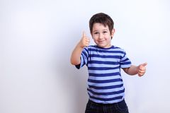 Cute happy boy showing thumbs up, studio shoot on white. Emotion Stock Photos