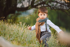 Cute happy boy on the street. Stylish baby boy having fun outside in the park. Cute happy boy child outdoors Royalty Free Stock Photos