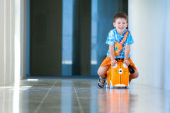 Cute happy boy with a suitcase at airport Royalty Free Stock Images