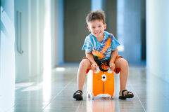 Cute happy boy with a suitcase at airport Royalty Free Stock Image