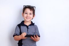 Cute happy boy using mobile phone. Child playing on smartphone. stock photography
