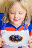 Cute, happy child eating a homemade healthy snack. Happy child eating a homemade healthy snack of a wholemeal pikelet with fresh blueberries royalty free stock images