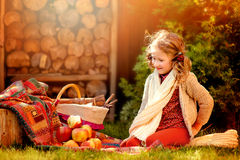 Cute happy child girl with apples sitting in sunny autumn garden near basket Royalty Free Stock Photography
