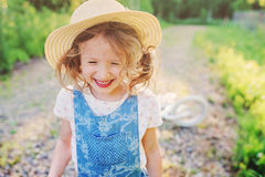 Cute happy child girl with bicycle on summer sunny road Royalty Free Stock Images