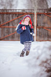Cute happy child girl with christmas candy in winter snowy garden Royalty Free Stock Photography