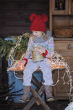 Cute happy child girl in christmas hat and sweater outdoor portrait. With lights and fir branches on background Royalty Free Stock Images