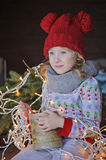 Cute happy child girl in christmas hat and sweater outdoor portrait Royalty Free Stock Photo