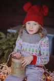 Cute happy child girl in christmas hat and sweater outdoor portrait. Cute happy child girl in christmas hat and sweater sitting with vintage box, lights and fir Stock Photography