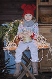 Cute happy child girl in christmas hat and sweater sitting outdoor. Cute happy child girl in christmas hat and sweater sitting on the table with vintage box, fir Stock Photo