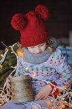 Cute happy child girl in christmas hat and sweater sitting outdoor. Cute happy child girl in christmas hat and sweater sitting with vintage box, lights and fir Stock Photos