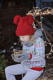 Cute happy child girl in christmas hat and sweater with wooden candle holder Stock Photography