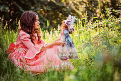 Cute happy child girl in fairytale princess dress playing with doll on the walk in summer Royalty Free Stock Image