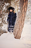 Cute happy child girl in fur hat and coat on the walk in winter snowy forest Royalty Free Stock Image