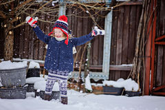 Cute happy child girl having fun and throwing snow in winter garden Stock Photos