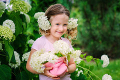 Cute happy child girl with hydrangea flowers bouquet in summer garden Royalty Free Stock Photo