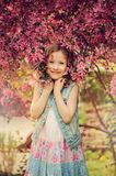 Cute happy child girl in jeans vest enjoying spring near blooming crab apple tree in country garden Royalty Free Stock Images