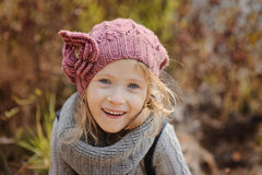 Cute happy child girl in knitted hat and snood portrait in autumn Royalty Free Stock Image