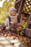 Cute happy child girl playing with basket of grapes in sunny autumn garden Stock Images