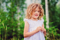 Cute happy child girl playing with grass on the walk in summer forest Stock Images
