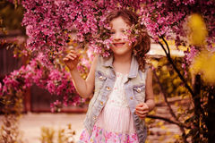 Cute happy child girl playing and hiding at blooming crabapple tree in spring garden Royalty Free Stock Photography