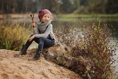 Cute happy child girl playing on the river side in autumn Stock Photos