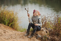 Cute happy child girl playing on the river side in autumn Royalty Free Stock Photo
