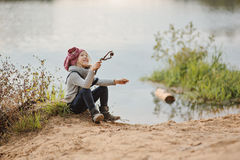 Cute happy child girl playing on the river side in autumn Stock Image