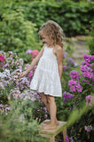 Cute happy child girl playing in summer blooming garden Royalty Free Stock Image