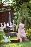 Cute happy child girl playing toy wash in summer sunny garden. Cute happy child girl in pink plaid dress playing toy wash in summer sunny garden Stock Photo