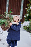 Cute happy child girl playing in winter snowy garden with basket of fir branches. Cute happy child girl in owl knitted hat playing in winter snowy garden with Stock Image