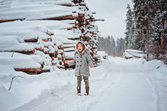 Cute happy child girl portrait on the walk in winter forest with tree felling on background Royalty Free Stock Photo