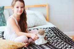 Cute happy child girl relaxing at home on the bed in her room in early morning. Smiling kid with teddy bear enjoying cozy weekend Stock Image