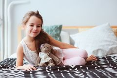Cute happy child girl relaxing at home on the bed in her room in early morning. Smiling kid with teddy bear enjoying cozy weekend Stock Photo