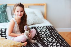 Cute happy child girl relaxing at home on the bed in her room in early morning. Smiling kid with teddy bear enjoying cozy weekend Stock Images