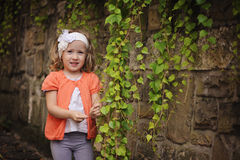 Cute happy child girl standing at old stone wall with green leaves Royalty Free Stock Photos