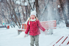 Cute happy child girl throwing snow and laughing on the walk in winter park Royalty Free Stock Photo