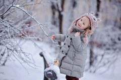 Cute happy child girl on the walk in winter snowy park Royalty Free Stock Photo